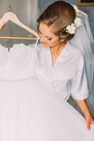 Beautiful sensual blonde bride in robe and white veil posing with wedding dress indoors Royalty Free Stock Photos