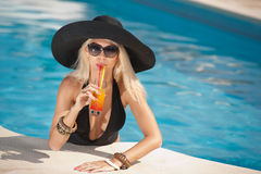 Beautiful sensual blonde with fashionable sunglasses relaxing in the pool with a juice. Attractive long hair woman in black Stock Photos