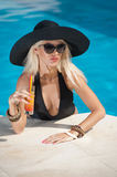 Beautiful sensual blonde with fashionable sunglasses relaxing in the pool with a juice. Attractive long hair woman in black Royalty Free Stock Images