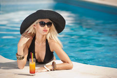 Beautiful sensual blonde with fashionable sunglasses relaxing in the pool with a juice. Attractive long hair woman in black Stock Image