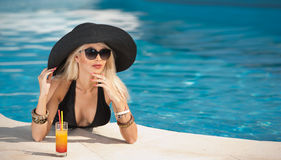 Beautiful sensual blonde with fashionable sunglasses relaxing in the pool with a juice. Attractive long hair woman in black Stock Photography
