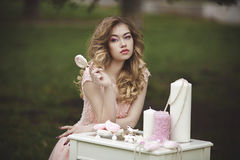 A beautiful, sensual blonde with a lollipop sits at a table with sweets and candles. Romantic mood. Portrait of a girl royalty free stock images