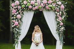 Beautiful and sensual blonde model girl with stylish wedding hairstyle in a white fashionable dress with a bouquet of royalty free stock photos