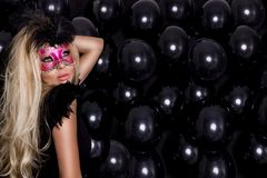 Beautiful sensual blonde woman with carnival mask , standing on a background of black balloons