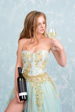 Beautiful sensual blonde woman in gorgeous long dress holding glass of white wine and bottle. Young girl celebrating Royalty Free Stock Image