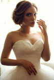 Beautiful sensual bride with dark hair in luxurious lace wedding dress royalty free stock photography