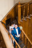 Beautiful sensual  bride hugging from behind her handsome groom holding book at the wooden stairs of old library Stock Photos