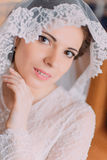 Beautiful sensual bride in wedding gown with lifted veil touching her face while posing indoors Royalty Free Stock Photos