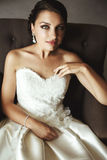 Beautiful sensual brunette bride in white dress sitting on leath Stock Photo