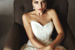 Beautiful sensual brunette bride in white dress sitting on leath Stock Images