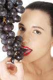 Beautiful sensual brunette eating grapes Royalty Free Stock Image