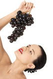 Beautiful sensual brunette eating grapes Stock Images
