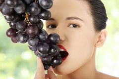 Beautiful sensual brunette eating grapes Stock Photos