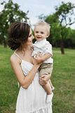 Beautiful and sensual brunette model girl in short white dress, with cute little stylish baby boy on her hands posing at green par. K stock photo