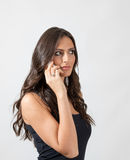 Beautiful sensual brunette woman with long hair talking on the smartphone looking away stock photography