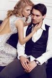 Beautiful sensual couple in elegant clothes posing in studio. Fashion studio photo of beautiful sensual couple in elegant clothes stock image