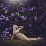 Beautiful sensual girl blonde in spring. Spring style. Blossoming spring garden. A young girl in a gold dress lies under. The blooming purple bushes. Creative royalty free stock photography