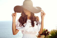 Beautiful sensual girl with dark hair in elegant dress and hat Stock Images