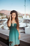 Beautiful sensual girl with long hair in fashion dress posing by Royalty Free Stock Photo