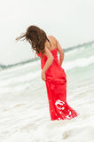 Beautiful sensual girl in water. Romantic Young beautiful woman on the beach in a red dress on the ocean coast Stock Image
