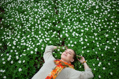 Beautiful sensual lady lying on flower meadow royalty free stock images