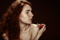 Beautiful sensual nude redhead woman posing with strawberry. Isolated on brown with copy space Royalty Free Stock Image