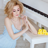 Beautiful sensual and sexy blonde girl in a blue dress sitting a. T the piano and looks down against a white brick wall Stock Images