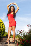 Beautiful and sensual South American woman arms up with red dress on the stairs outdoor Stock Photography