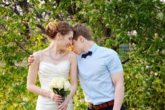 Beautiful sensual wedding couple and gentle bouquet of flowers. Groom hugging lovely bride outdoors Royalty Free Stock Images