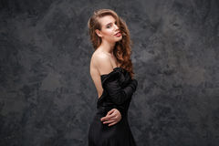 Beautiful sensual woman in black evening dress with open back Royalty Free Stock Image