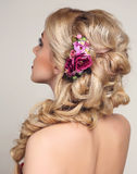 Beautiful sensual woman with blond curly hair and flower's accessory Stock Image