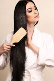 Beautiful sensual woman combing her luxurious healthy hair Stock Photography