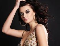 Beautiful sensual woman with dark hair with bijou in luxurious dress. Fashion studio photo of beautiful sensual woman with dark hair and bright makeup wearing Royalty Free Stock Image