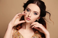 Beautiful sensual woman with dark hair and bright makeup, with bijou Stock Photography