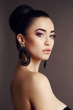 Beautiful sensual woman with dark  hair and bright makeup, with bijou. Fashion studio portrait of beautiful sensual woman with dark  hair and bright makeup, with Royalty Free Stock Photography