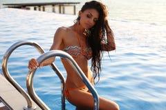 Beautiful sensual woman with dark hair in elegant bikini. Fashion outdoor photo of beautiful sensual woman with dark hair wearing elegant bikini, posing beside Royalty Free Stock Image
