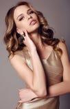 Beautiful sensual woman with dark hair in elegant gold dress royalty free stock images