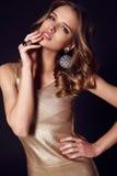 Beautiful sensual woman with dark hair in elegant gold dress Stock Photography
