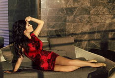 Beautiful sensual woman with dark hair wearing elegant red dress Stock Photography