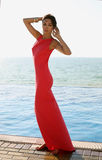 Beautiful sensual woman with dark hair wears elegant red dress Stock Photography