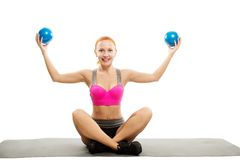 Beautiful sensual woman doing fitness with balls. Young slim sensual red woman wearing sports bra practicing fitness Stock Photos