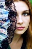 Beautiful sensual woman hiding behind fan stock photo