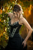 Beautiful sensual woman with roses in hair posing near a wall of green leaves. Young female in black elegant dress daydreaming Stock Photography