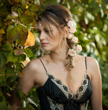Beautiful sensual woman with roses in hair posing near a wall of green leaves. Young female in black elegant dress daydreaming Royalty Free Stock Photos
