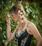 Beautiful sensual woman with roses in hair posing near a wall of green leaves. Young female in black elegant dress daydreaming Royalty Free Stock Photography