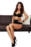 Beautiful sensual woman sitting on a sofa Royalty Free Stock Photo