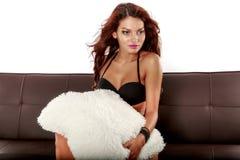 Beautiful sensual woman sitting on a sofa Royalty Free Stock Photography