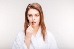 Beautiful sensual woman trying red lipstick on half of lips Royalty Free Stock Image