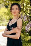 Beautiful Sensual Woman With Dark Hair In Elegant Clothes Posing In Garden With Flowering Wisteria Trees Stock Photo