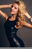 Beautiful sensual woman wtih blond curly hair in elegant black dress Stock Images